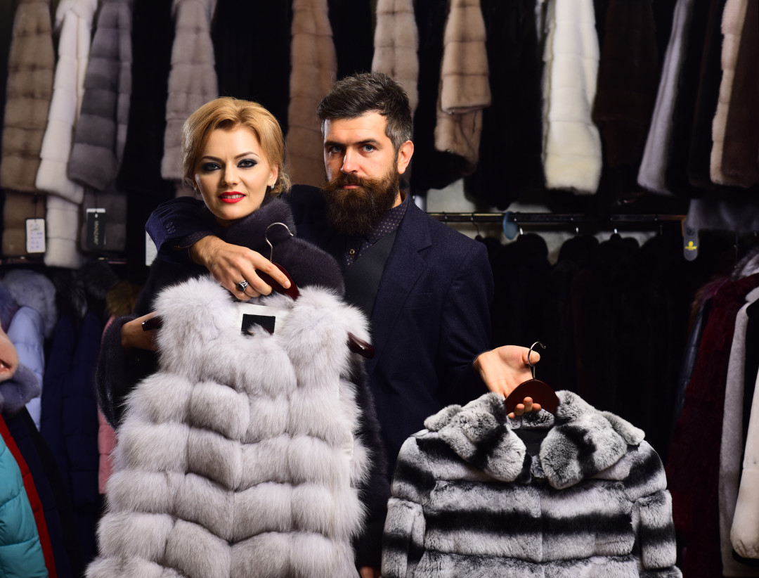 Man with strict face and woman with coats in fur shop. Woman with smiling face in black fur coat with bearded man. Couple in love holds white sable and chinchilla fur coats. Luxury shopping concept.